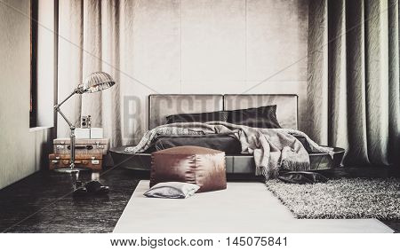 Stylish modern bedroom interior with grey decor and rugs thrown over a double bed with ottoman and long drapes on either side. 3d Rendering.