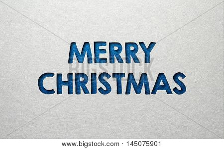 Merry Christmas card or invitation design in textured blue indented text on a grey background with copy space for your seasonal greeting