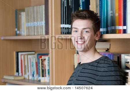 Happy smiling student in a college library looking at camera