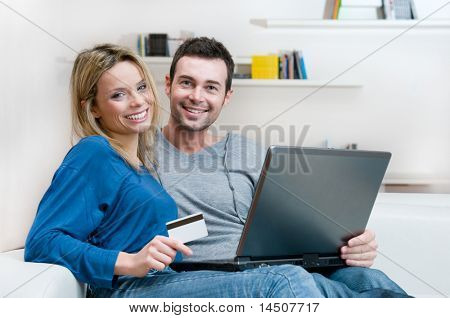 Smiling young couple making shopping online with credit card and laptop at home
