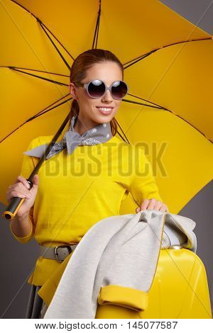 Glamour woman with yellow umbrella and suitcase