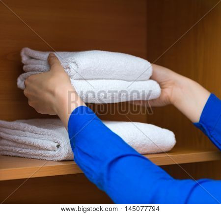 Room Service. Woman Changing Towels In Cabinet.