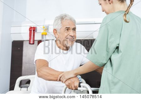 Nurse Helping Smiling Senior Man In Using Walker