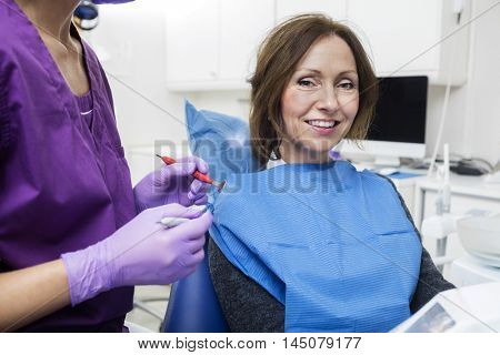 Smiling Female Patient By Dentist Holding Tools