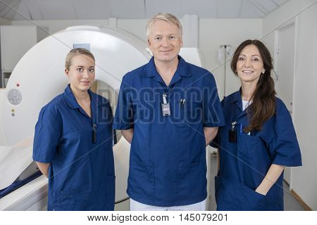 Confident Medical Team Smiling While Standing By MRI Machine