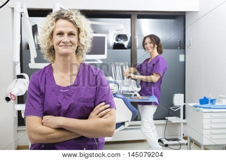 Assistant Standing Arms Crossed With Colleague Working In Dentis