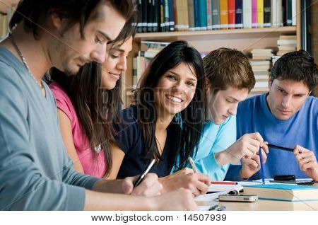 Group of young students working and studying in a college library, smiling girl looking at camera.