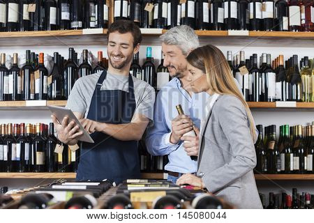 Salesman Showing Wine Information To Customers On Digital Tablet