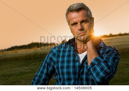 Mature man relax and looking at camera with satisfaction in the wonderful light of the sunset