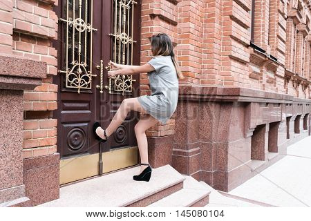Young woman in short gray dress and shoes with heels pulling the handle of vintage door leaning into her leg