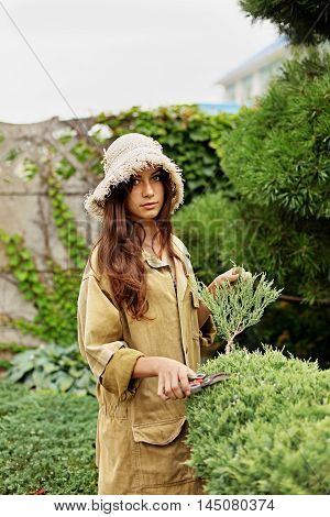 Girl gardener in working clothes and straw hat cuts garden scissors evergreen. She looks into the camera.
