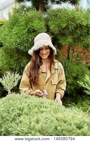 Girl gardener in working clothes and straw hat cuts garden scissors evergreen. She`s smiling.