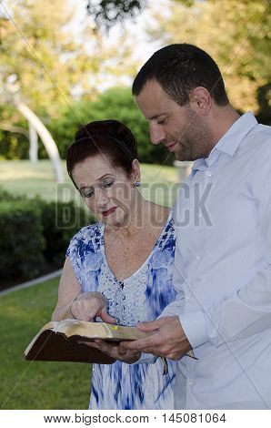 Mother and adult son reading the Bible together going over scripture.