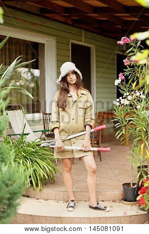 Beautiful girl with long hair gardener in working clothes standing with a large garden scissors in his hand. On her head wearing a straw hat.