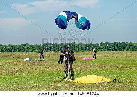 Kharkiv Ukraine - August 20 2016: Skydiver unfasten his parachute after landing at the airfield Korotych Kharkov region Ukraine on August 20 2016