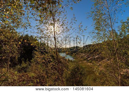 Sunset At Quarry Or Lake Or Pond With Sandy Beach, Green Water, Birch On A Foreground