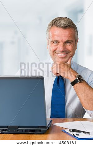 Happy smiling mature businessman looking at camera and working in his modern office