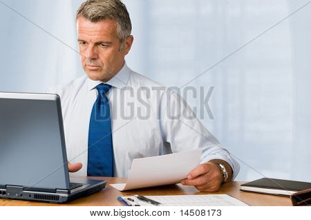 Mature businessman looking and analyzing document in his modern office at work