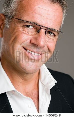 Smiling mature man looking at camera with a pair of glasses