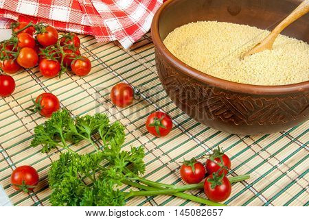 Selection of ingredients for cooking couscous: tomatoes, couscous, herbs
