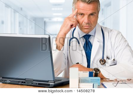 Serious mature doctor looking and gazing at you while working with  laptop and medication's cases to make prescriptions in his clinic office
