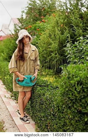 Cute girl with long hair cutting boxwood with electrical hedge trimmer. She is wearing a straw hat and work clothes.
