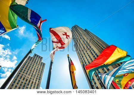 Concept photo of global international corporate business. Skyscrapers and international flags against blue sky at sunny day. Business city district.