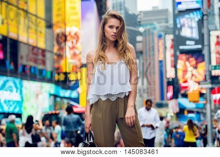 Beautiful blonde fashionable model girl standing in New York City Time square wearing fashionable summer outfit with white t-shirt and holding leather bag. Female summer trend 2016.