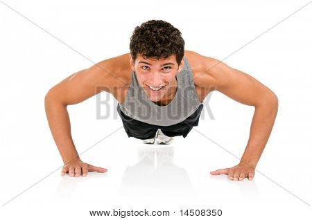 Young smiling fitness man doing push ups on floor, studio shot isolated on white background