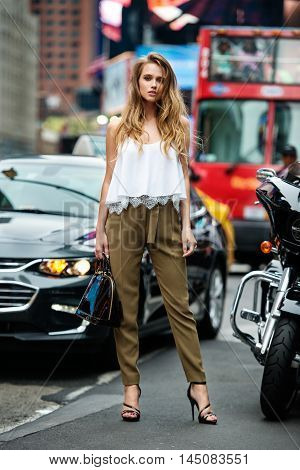 Beautiful fashionable woman standing on city street on car traffic wearing green pants white sexy t-shirt and holding bag. Girl traveling and shopping in New York CIty at summer.