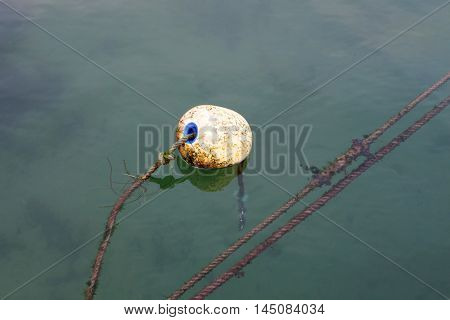 Dirty round buoy in the sea to signal
