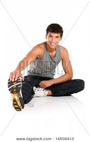 glücklich lächelnd junge Fitness Mann sitzt und, stretching-Übungen nach gymnastik isoliert auf weiss