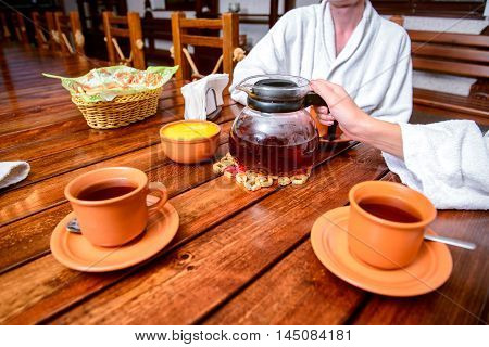Happy young couple drinking tea with honey at the hotel after healthy recreation procedure wearing white bathrobe
