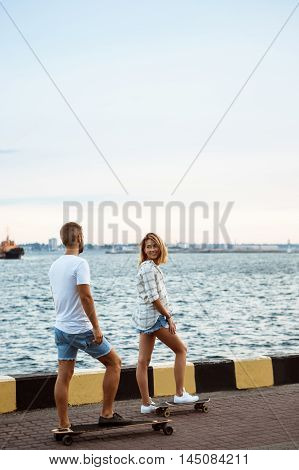 Young beautiful couple walking at seaside, smiling, skateboarding. Outdoor background