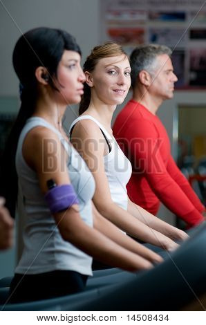 junge Frau Lächeln in die Kamera während des Gehens auf einem Laufband in Fitnessstudio