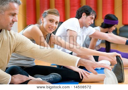 Smiling girl looking at camera during stretching exercises with her class at gym