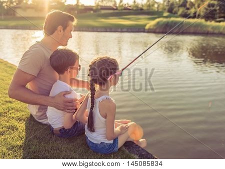 Back view of handsome father and his beautiful little kids catching fish in the pond using a fishing rod sitting on the ground
