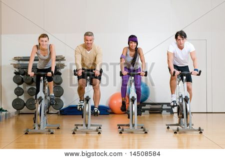 Happy active people exercising with bicycles in a gym. Front view