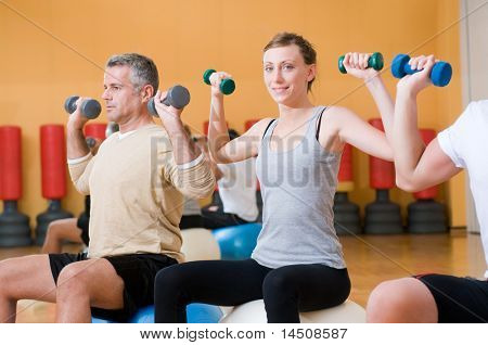 Young lady smiling and looking at camera while lifting weigths on a fitness ball at gym