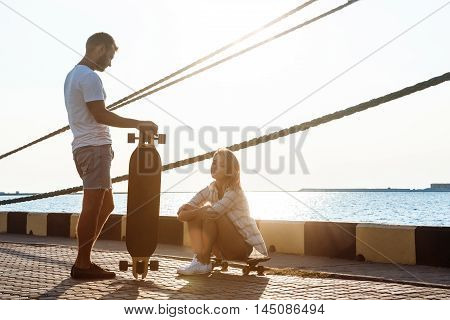 Young beautiful couple walking at seaside, skateboarding. Outdoor background.