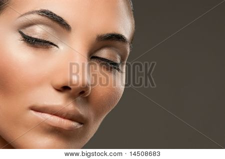 Closeup shot of beautiful female model with professional fashion makeup posing over gray background