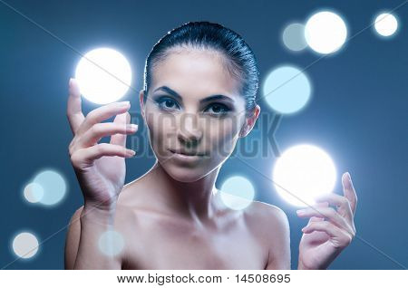 Beautiful fairy female model holding sphere of light on her hands, professional beauty makeup