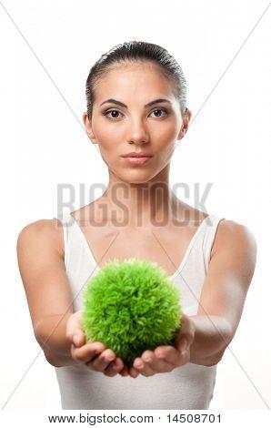 Bela jovem segurando uma esfera de grama verde, símbolo de cuidado e proteção do natural