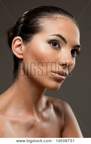 Fashion and beauty model portrait over gray background, perfect professional makeup
