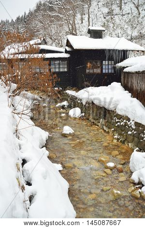 Small river flowing by an onsen in winter in Akita Japan.