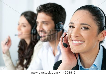 Beautiful young lady talking on headset at call center office