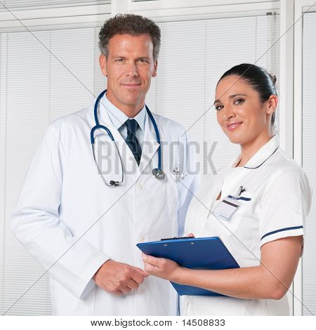 Mature doctor and his female assistant smiling together at hospital