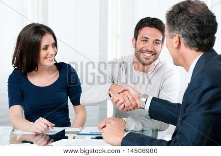 Feliz pareja sellar un acuerdo con su asesor financiero personal en casa