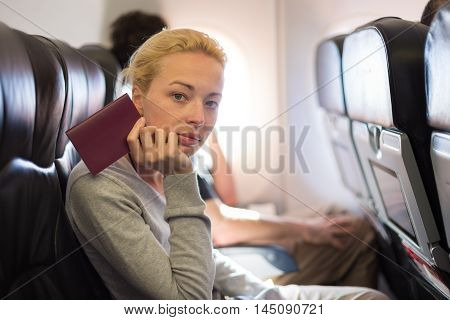 Woman flying by commercial airplane, sitting on her seat, holding passport in her hand, waiting to arrive at immigration point.