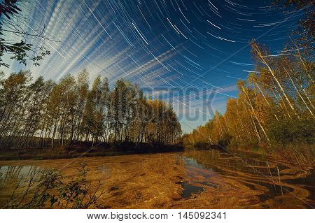 Star And Cloud Trails Over Lake